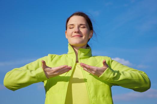 Junge Frau macht Atemübungen im Freien